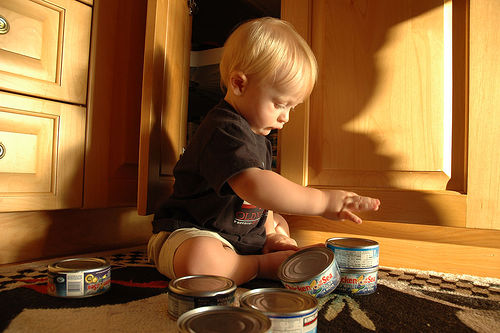 child stacking tuna cans