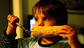 kid eating corn